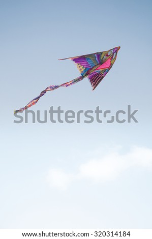 A decorative kite flying high in the clear sky.