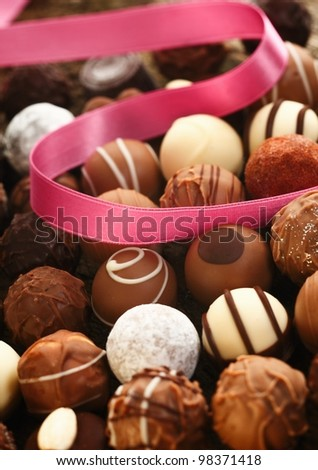 A decorative pink ribbon lies twirled over handmade spherical chocolates with different patterns in a gift and celebration concept