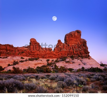 A Deep Blue Evening Sky And Full Moon Rising Over Red Sandstone Rock Forms At Arches National Park, Utah, USA - stock photo