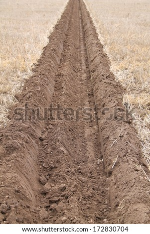 A Deep Ploughed Furrow on a Farmers Field. - stock photo