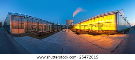 A 180 degree panoramic image of several huge glasshouses at dusk