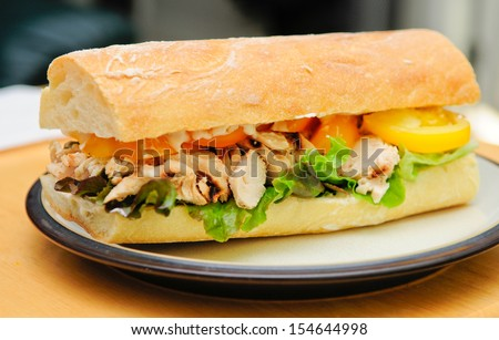 a delicious bbq chicken sandwich on french bread with tomatoes and lettuce - stock photo