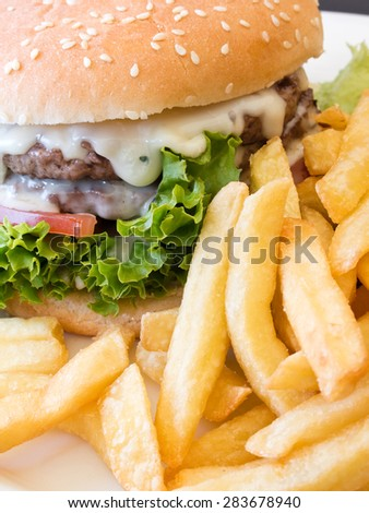 A delicious burger dripping with cheese together with crispy french fries - stock photo