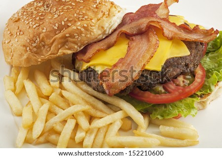 A delicious cheese burger with bacon and french fries - stock photo