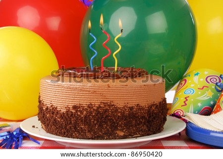 A delicious chocolate birthday cake with three candles and balloons