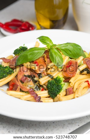 A delicious fresh gourmet Italian strozzapreti pasta dish, with pancetta, italian sausage, broccoli, vegetables, topped with fresh basil.