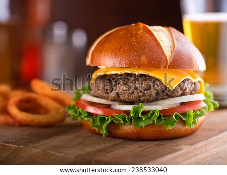 A delicious gourmet cheeseburger on a pretzel bun with lettuce, onion, and tomato. - stock photo