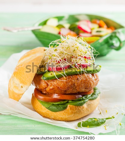 A delicious gourmet hamburger with fresh vegetables: tomato, spinach, pickles, radish and sprouts