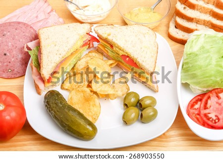 A delicious ham, cheese, lettuce and tomato sandwich with mustard and mayo on a plate with a dill pickle, potato chips and olives, with ingredients on wood cutting board - stock photo