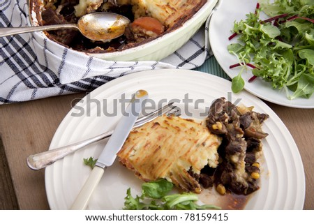 A delicious home made meat pie on a wooden table that makes your mouth water. - stock photo