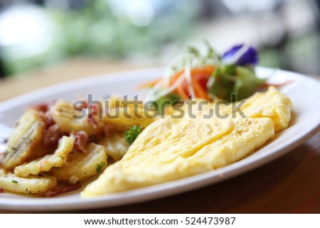 A delicious home style breakfast with crispy bacon, eggs omelette