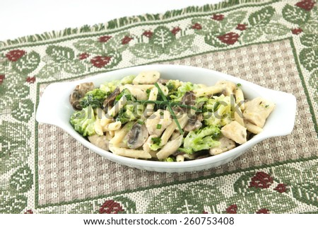A delicious Italian meal, chicken pasta primavera, with chicken, broccoli, penne pasta, mushrooms in a creamy alfredo sauce - stock photo