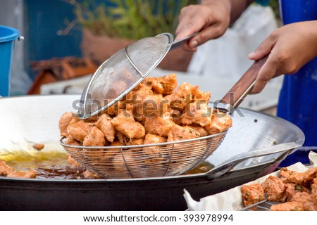 A delicious-looking spicy fried food or fried fish patty from a boiling pan of a roadside food stall in Thailand - stock photo