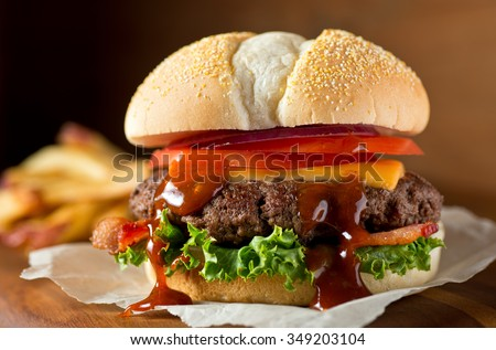 A delicious messy homemade bacon cheeseburger with barbecue sauce, lettuce, tomato, and onion. - stock photo