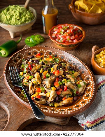 A delicious mexican mussel salad ceviche with red pepper, corn, black beans, green onion, cilantro, and jalapeno pepper. - stock photo