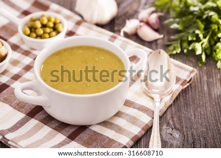 A delicious pea cream with aromatic spices on a wooden table. Studo shot - stock photo