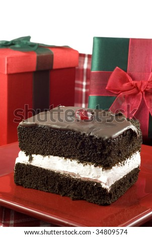 A delicious piece of chocolate three layer cake with holiday gifts, vertical with white background and copy space - stock photo