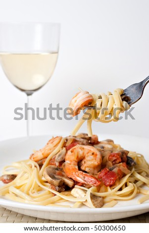 A delicious shrimp scampi pasta dish along with a glass of pinot grigio white wine.  Shallow depth of field with focus on the fork. - stock photo