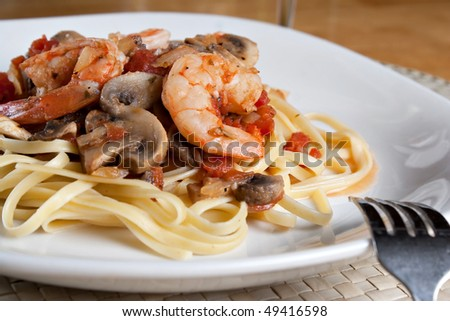 A delicious shrimp scampi pasta dish with mushrooms and diced tomatoes on a white plate. - stock photo