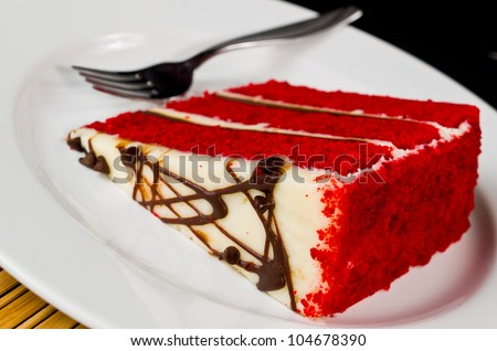A Delicious Slice of Layered Red Velvet Cake with a Fork - stock photo