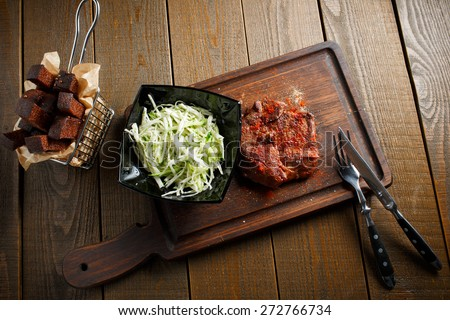 A delicious steak with red chili pepper, black plate of salad with fresh cabbage and rye toast croutons on wooden brown background - stock photo