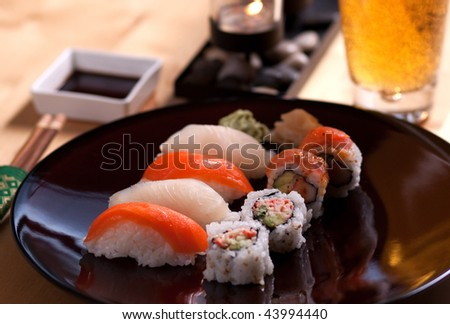 A delicious sushi meal is laid out on a table with a beer. - stock photo