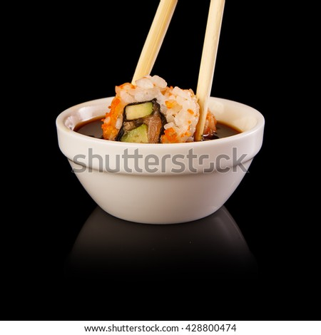A delicious sushi roll dipped in sauce on a black background. - stock photo