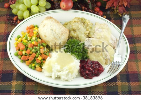 A delicious Thanksgiving dinner with turkey, dressing, mashed potatoes with gravy, mixed vegetables, and rolls - stock photo