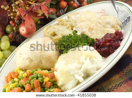 A delicious Thanksgiving turkey dinner on a platter, closeup with selective focus, horizontal with diagonal viewpoint - stock photo