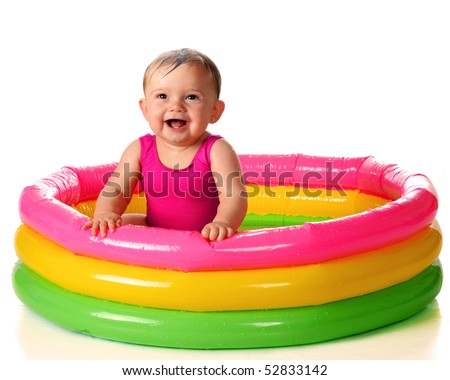 A delighted baby girl playing in a water-filled kiddie pool.  Isolated on white. - stock photo
