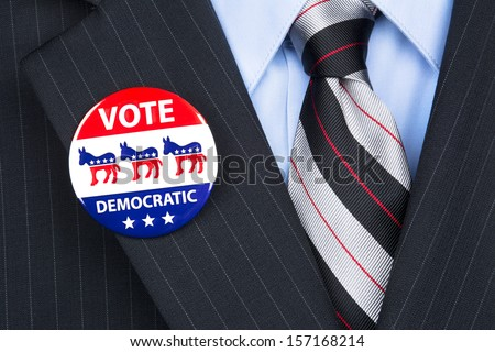 A democratic voter proudly wears his party badge on his suit lapel - stock photo