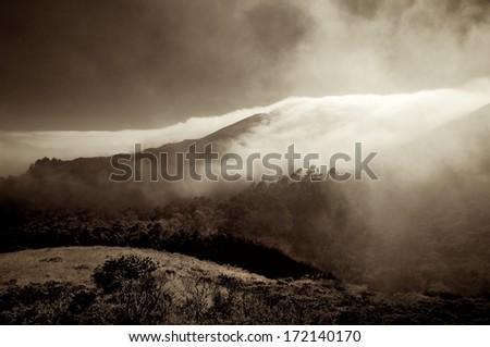 A dense layer of marine fog slowly envelopes the ridges along the Marin headlands - stock photo