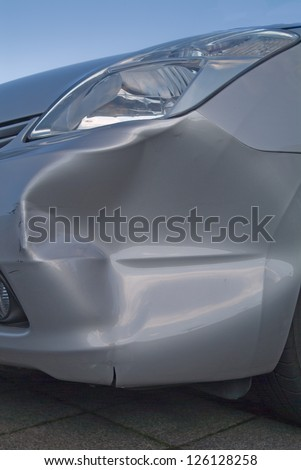 A dent in the right front quarter of a european car