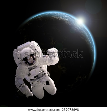 A depiction of an astronaut floating in outer space. An Earth-like planet sees sunrise in the background. Elements of this Image Furnished by NASA.