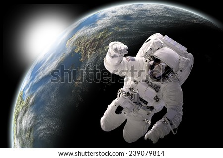 A depiction of an astronaut floating in outer space. An Earth-like planet sees sunrise in the background. Elements of this Image Furnished by NASA. - stock photo