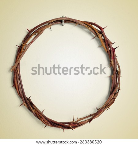 a depiction of the Crown of Thorns of Jesus Christ hanging from a nail on a wall, with a retro effect - stock photo