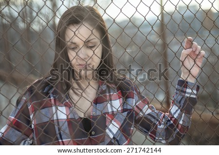 A depress woman in front of a fense - stock photo