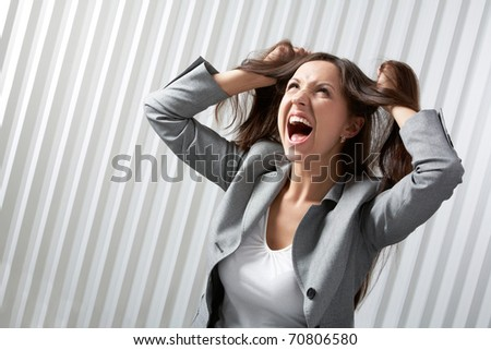 A depressed businesswoman screaming and tousling her hair - stock photo