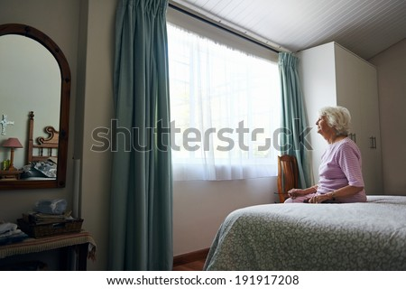 A depressed elderly widow sitting on her bed looking out the window - stock photo