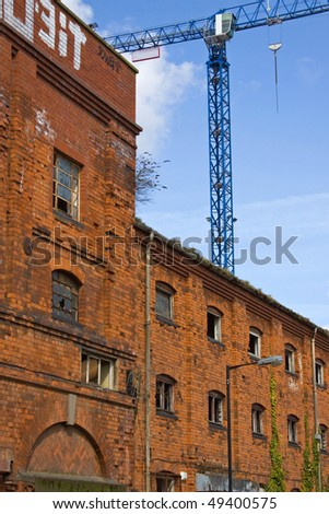 A derelict building in the lee of a tower crane on an urban renewal site - stock photo