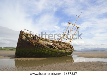 A derelict fishing boat lit by evening sunshine at Ettrick Bay, Bute - stock photo