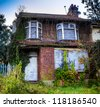 A derelict house with ivy growing over it - stock