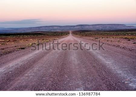 A desert road in Namibia - sunset light. - stock photo