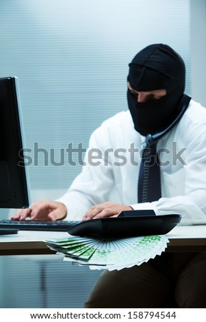 A desk clerk wearing a balaclava while doing some swindle about money (focus on the money)