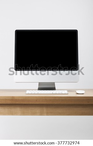 A desk top(computer, pc) with black(empty, blank, vacant, hollow) screen with wireless keyboard, mouse on the wood desk(table) - stock photo