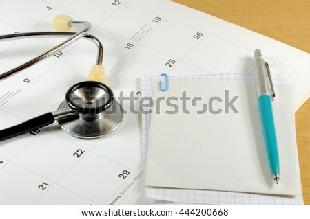 A desk top with stethoscope, notebook, pen and calendar - stock photo