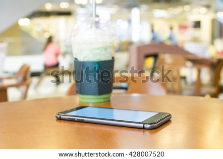 A desk with a smartphone - stock photo
