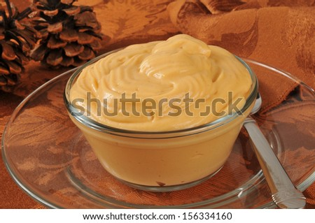 A dessert cup of butterscotch pudding on a Thanksgiving dinner table