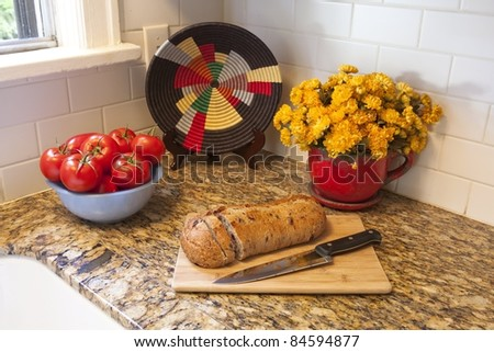 A detail in a kitchen of tomatoes, a potted plant, decorative plate and bread on a cutting board - stock photo