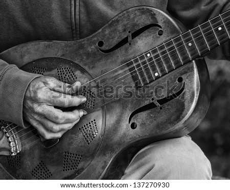 A detail picture of a guitar playing man with a metal - guitar. black abd White high contrast picture - stock photo